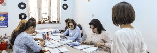 Birou în care se află mai multe asistente medicale generaliste carfe învașă limba germană