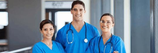 3 Asistenți Medicali, 2 fete și un băiat care sunt îmbrăcați în albastru, doi dintre ei având câte un stetoscop la gât