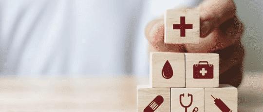 Mâna unui doctor care lucrează în sistemul sanitar german și care construiește o piramidă din minicuburi de lemn pe care se află diverse semne (o cruce de la salvare, o trusă de prim ajutor, o seringă, un stetoscop, un plasture și o picătură de apă)
