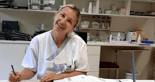 Asistentă Medicală îmbrăcată în alb, care se află la un birou într-un cabinet medical din Germania