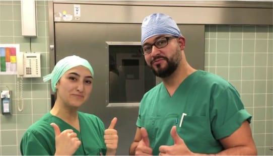 Doi asistenți medicali îmbrăcați în verde, bărbat și femeie care se află într-o sală de operații.