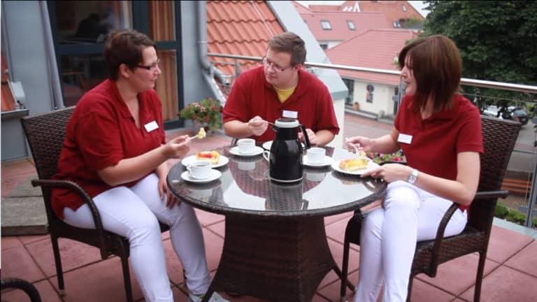 3 Asistenți Medicali, două femei și un bărbat, îmbrăcați în tricouri vișinii și pantaloni albi care se află în jurul unei mese și servesc micul dejun împreună