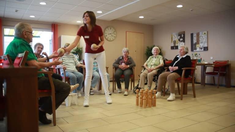 Asistentă medicală care lucrează la o Reședință de seniori MediClub Germania care face diverse jocuri cu bătrânii din centru