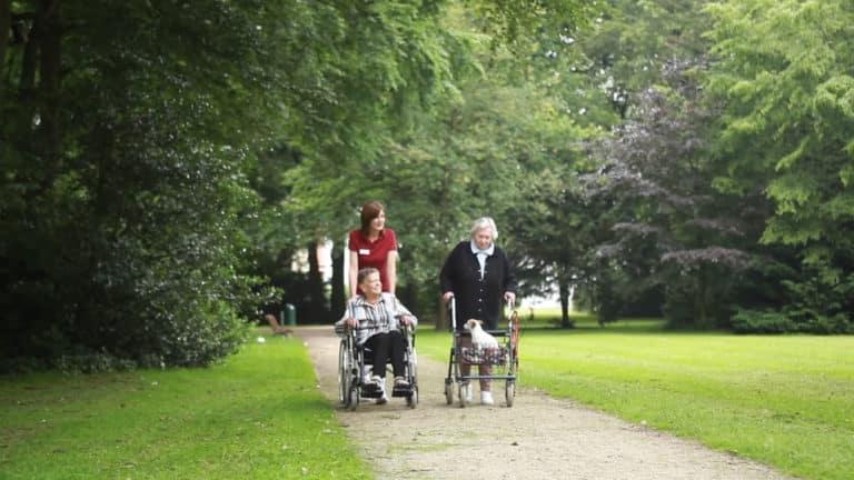 Curte a unei reședințe de seniori MediClub Germania în care se află o asistentă medicală care îîmpinge un cărucior cu rotile în care se află o bătrânp și lângă pe alee tot mergând se află o bătrână care împinge un cărucior cu un cățel